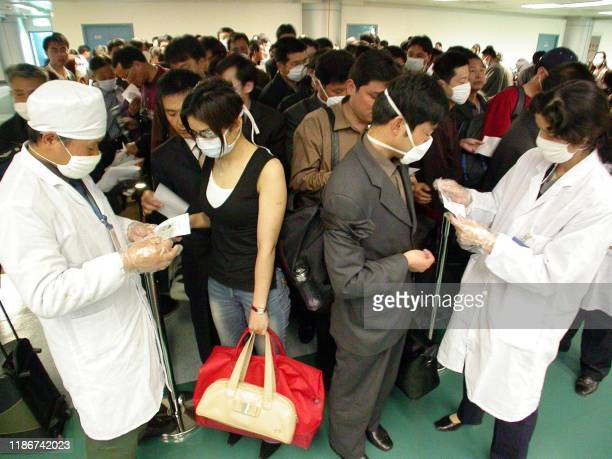 Chinese health officials check the health declarations by passengers boarding flights at the Nanjing airport 25 April 2003. China announced Friday...