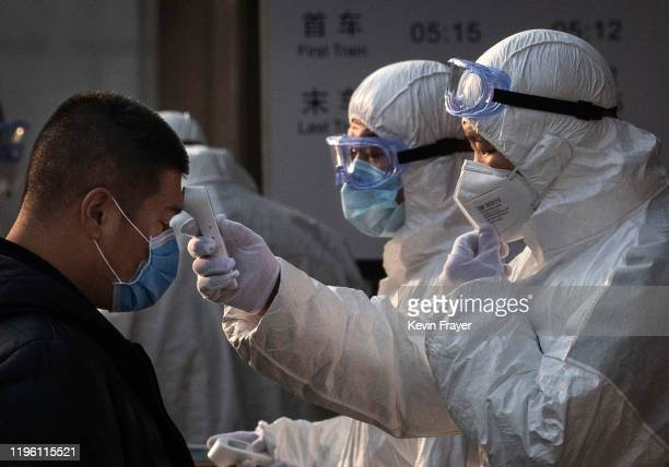 Chinese health worker checks the temperature of a woman entering a subway station during the Chinese New Year and Spring Festival on January 25, 2020...