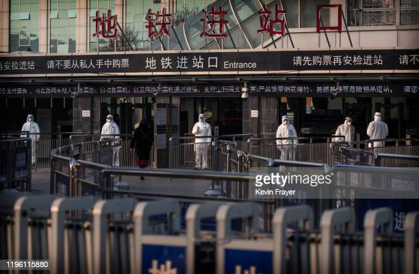 Chinese health workers wait to check the temperature of travellers entering a subway station during the Chinese New Year and Spring Festival on...