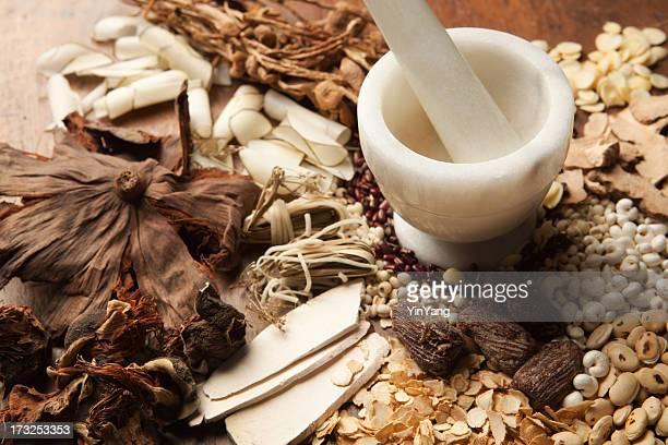chinese herbal medicine with mortor and pestle on wood hz - herb stock pictures, royalty-free photos & images