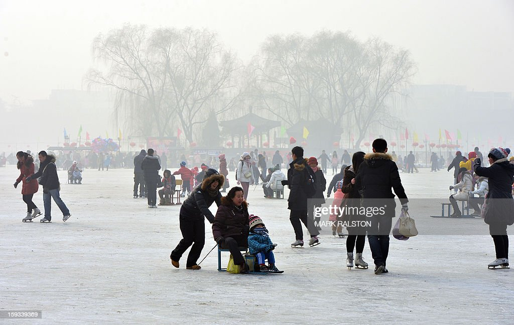 Chinese holidaymakers ride sleds on the frozen Houhai Lake in Beijing on January 12, 2013. The lake attracts scores of tourists and locals who use its frozen surface for skating, ice swimming and even exercising their dogs despite winter temperatures of up to minus 18 Celsius (0 F). AFP PHOTO/Mark RALSTON