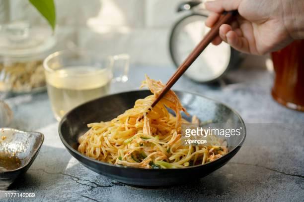 noodles cinesi fatti in casa:noodles piccanti mescolati con carne di pollo triturata - noodle foto e immagini stock