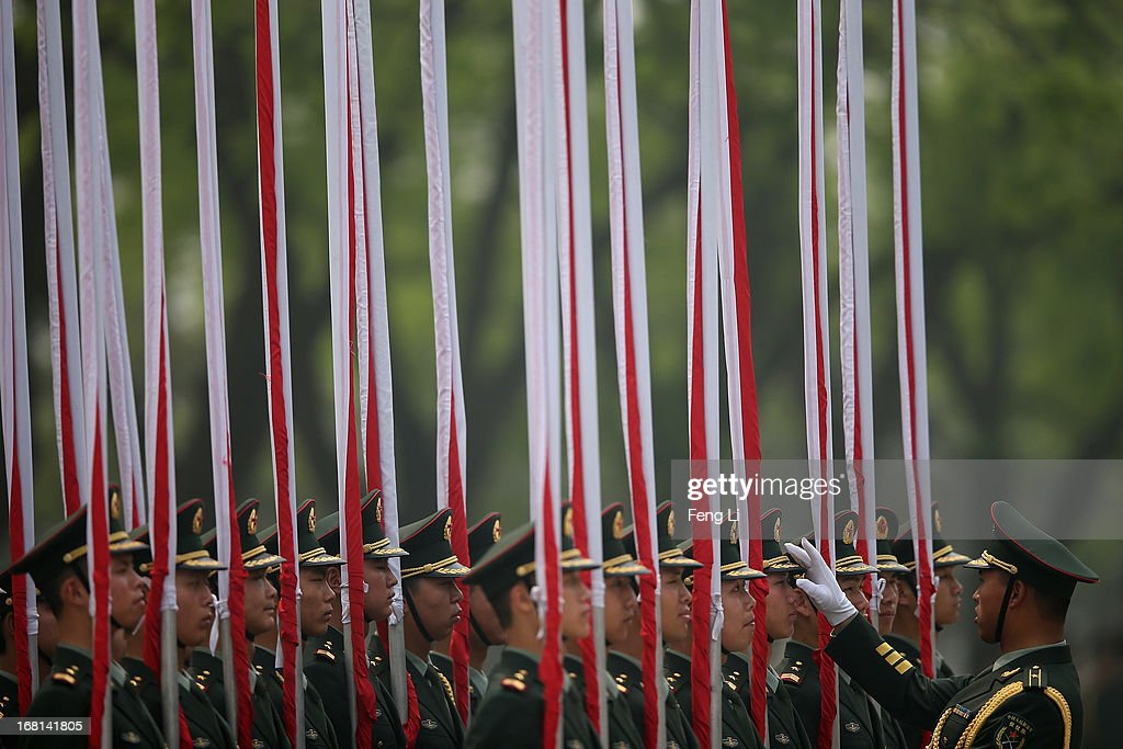 Chinese honor guards adjust their attire before a welcome ceremony for visiting Palestinian President Mahmoud Abbas outside the Great Hall of the People on May 6, 2013 in Beijing, China.