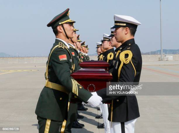 TOPSHOT Chinese honor guards receive caskets containing the remains of Chinese soldiers from South Korean honor guards during the handing over...