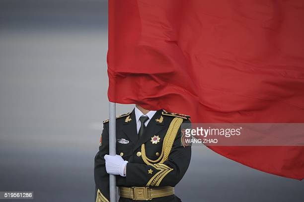 Chinese honour guard's face covered by a red flag as he prepares for the arrival of Sri Lanka Prime Minister Ranil Wickremesinghe and Chinese Premier...