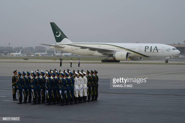 Chinese honour guards stand their guard as a plane carrying Pakistan's Prime Minister Nawaz Sharif lands at Beijing Capital International Airport on...
