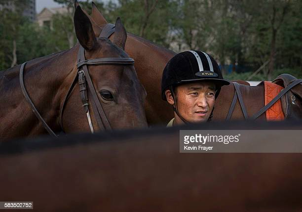 Chinese horse trainer stands with polo horses during an exhibition match between Chinese players from the Metropolitan Polo Club team and visiting...