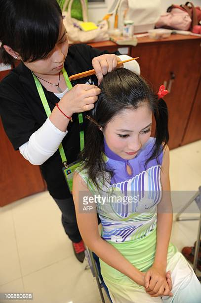 """Chinese hostess gets her hair done before attending a medal ceremony for the 16th Asian Games in Guangzhou on November 15, 2010. Nicknamed """"Asian..."""