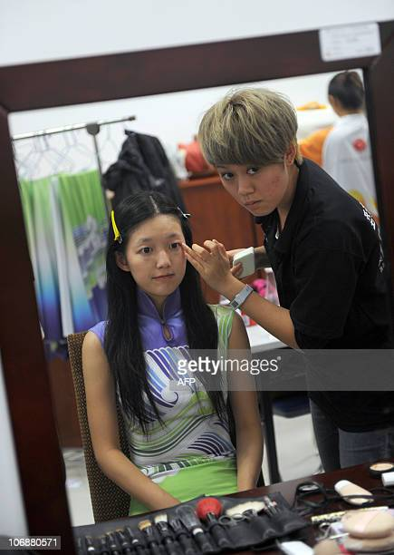 """Chinese hostess gets make up before attending a medal ceremony for the 16th Asian Games in Guangzhou on November 15, 2010. Nicknamed """"Asian Angels""""..."""