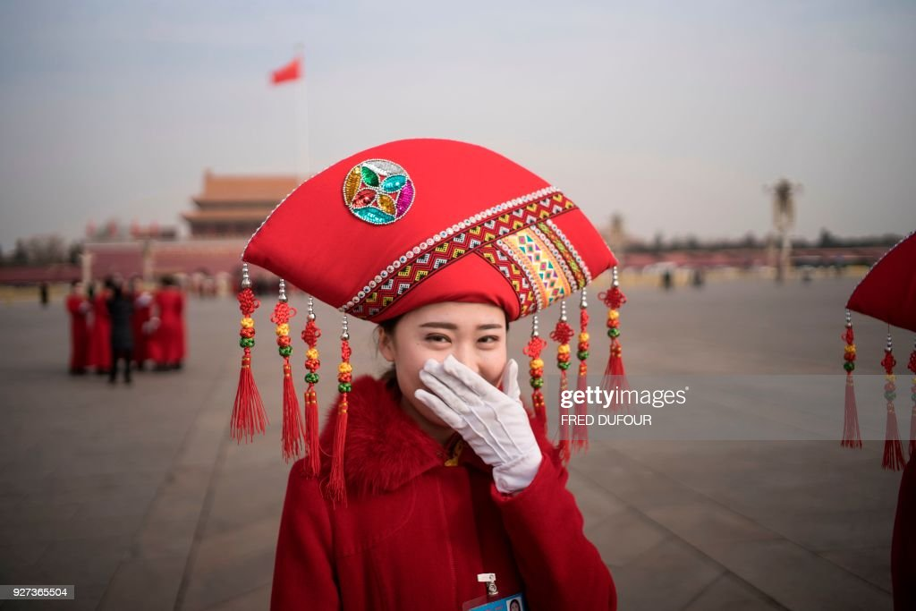 Chinese hostess reacts at Tiananmen square during the opening session of the National People's Congress, China's legislature, in Beijing on March 5, 2018. China's rubber-stamp parliament opens a major annual session set to expand President Xi Jinping's considerable power and clear him a path towards lifelong rule. /