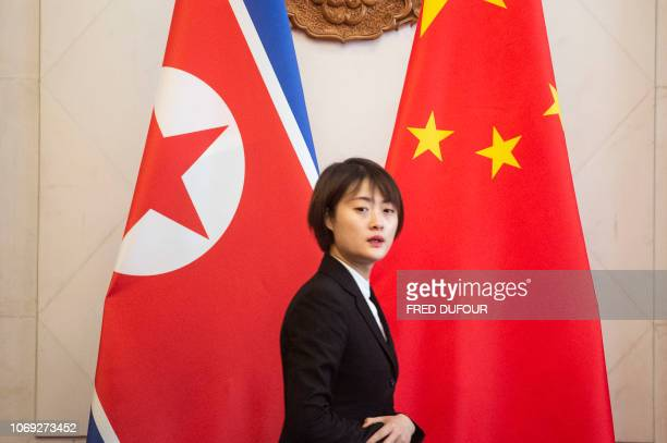 A Chinese hostess walks past North Korean and Chinese national flags before a meeting between North Korean Foreign Minister Ri Yong Ho and China's...