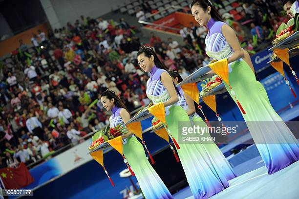 Chinese hostesses hold medals during a ceremony of the Men's qualification and team final in the Artistic Gymnastics at the 16thAsian Games in...