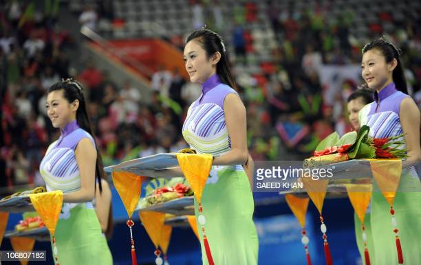 Chinese hostesses hold medals during a ceremony of the Men's qualification and team final in the Artistic Gymnastics at the 16th Asian Games in...