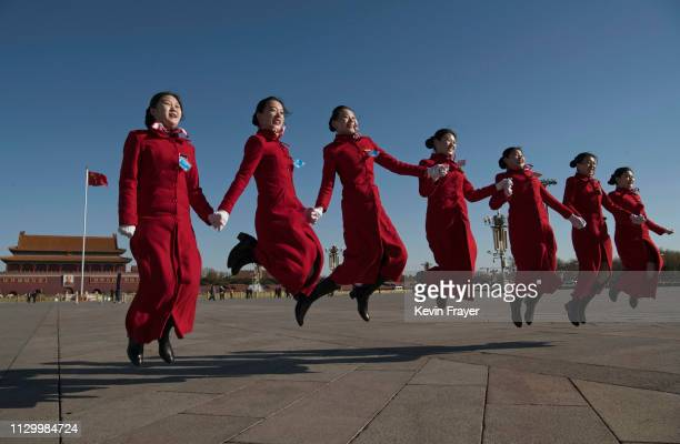 Chinese hostesses jump in the air at the request of a group of delegates taking pictures before the third plenary session of the National People's...