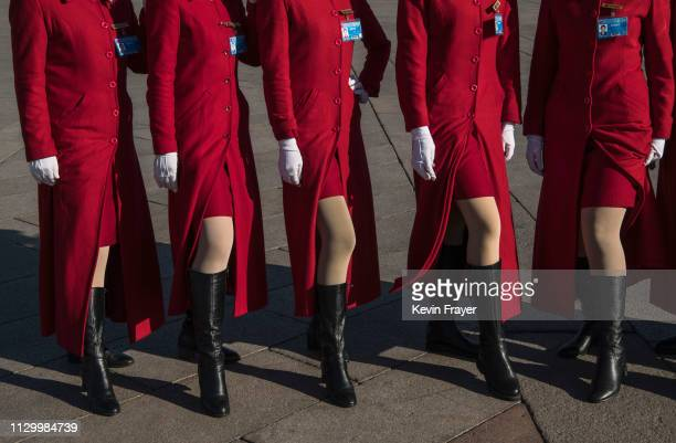 Chinese hostesses pose at the request of a group of delegates taking pictures before the third plenary session of the National People's Congress at...