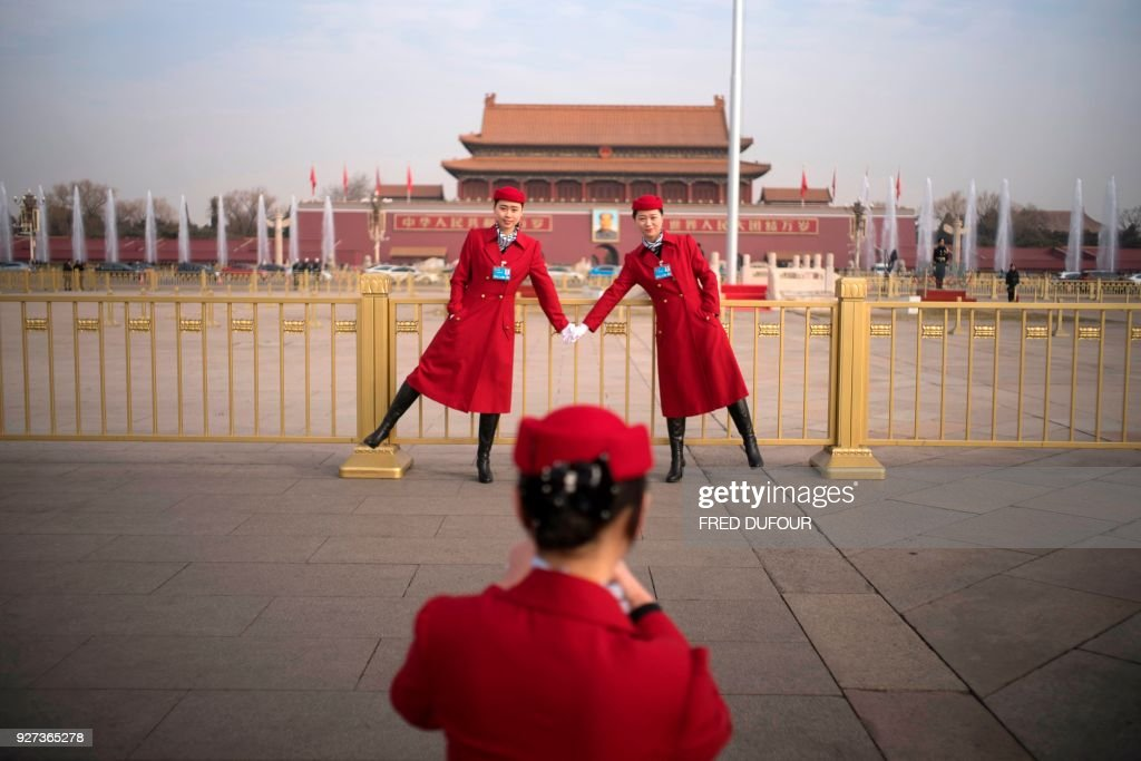 TOPSHOT - Chinese hostesses pose at Tiananmen square during the opening session of the National People's Congress, China's legislature, in Beijing on March 5, 2018. China's rubber-stamp parliament opens a major annual session set to expand President Xi Jinping's considerable power and clear him a path towards lifelong rule. /