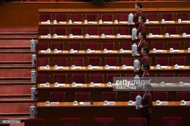 TOPSHOT Chinese hostesses prepare for the closing session of the Chinese People's Political Consultative Conference at the Great Hall of the People...