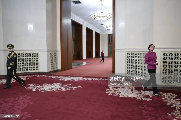 Chinese hostesses preprare for the opening session of the National People's Congress China's legislature in Beijing's Great Hall of the People on...