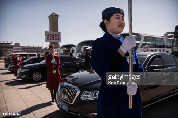 Chinese hostesses stand with signs next to Chinese made Hongqi luxury cars for delegates after the third plenary session of the National People's...