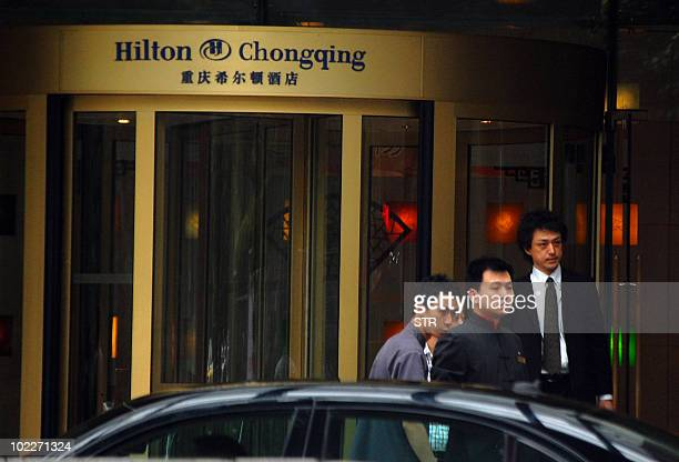 Chinese hotel staff see off the last remaining guest as police in southwest China's Chongqing municipality shut down the local Hilton Hotel on June...