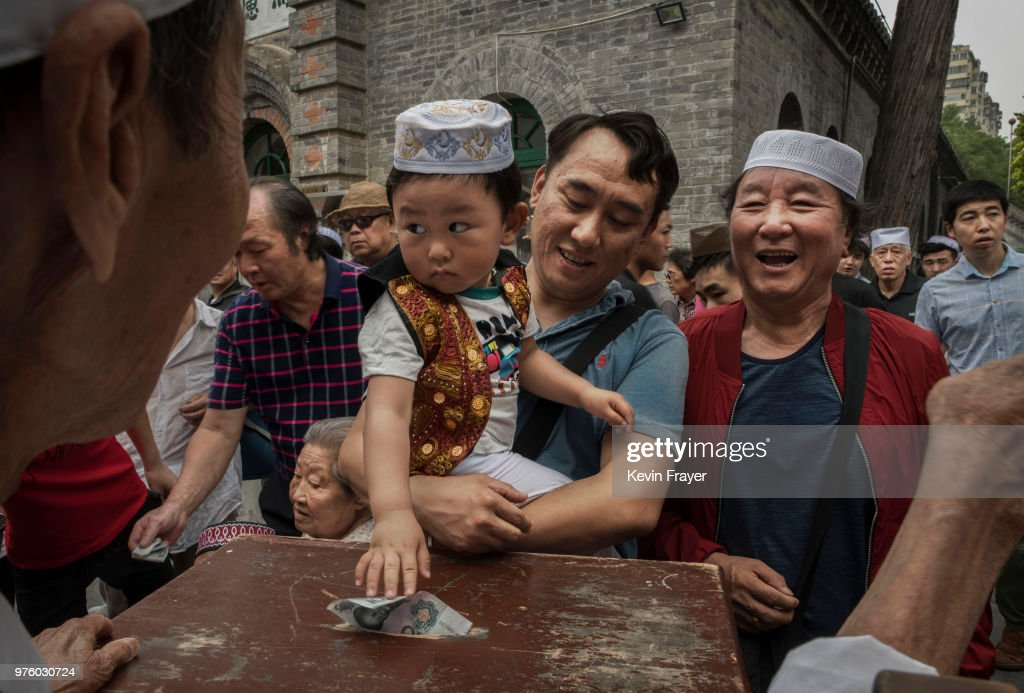 A Chinese Hui Muslim boy puts money into a donation box before Eid al-Fitr prayers marking the end of the holy fasting month of Ramadan at the historic Niujie Mosque on June 16, 2018 in Beijing, China. Islam in China dates back to the 10th century as the legacy of Arab traders who ventured from the Middle East along the ancient Silk Road. Of an estimated 23 million Muslims in China, roughly half are Hui, who are ethnically Chinese and speak Mandarin. China's constitution provides for Islam as one of five 'approved' religions in the officially atheist country though the government enforces severe limits. Worship is permitted only at state-sanctioned mosques and proselytizing in public is illegal. The Hui, one of 55 ethnic minorities in China (along with the Han majority), have long nurtured a coexistence with the Communist Party and is among the minority groups with political representation at various levels of government. The Hui Muslim population fast from dawn until dusk during Ramadan and it is believed there are more than 20 million members of the community in the country.