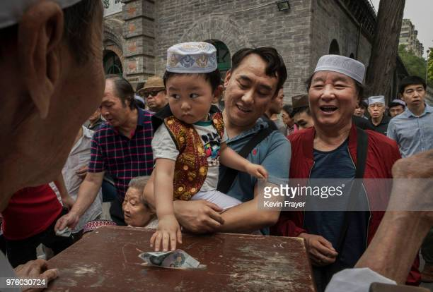 Chinese Hui Muslim boy puts money into a donation box before Eid al-Fitr prayers marking the end of the holy fasting month of Ramadan at the historic...