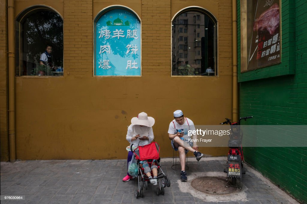 A Chinese Hui Muslim couple sit outside a restaurant after Eid al-Fitr prayers marking the end of the holy fasting month of Ramadan at the historic Niujie Mosque on June 16, 2018 in Beijing, China. Islam in China dates back to the 10th century as the legacy of Arab traders who ventured from the Middle East along the ancient Silk Road. Of an estimated 23 million Muslims in China, roughly half are Hui, who are ethnically Chinese and speak Mandarin. China's constitution provides for Islam as one of five 'approved' religions in the officially atheist country though the government enforces severe limits. Worship is permitted only at state-sanctioned mosques and proselytizing in public is illegal. The Hui, one of 55 ethnic minorities in China (along with the Han majority), have long nurtured a coexistence with the Communist Party and is among the minority groups with political representation at various levels of government. The Hui Muslim population fast from dawn until dusk during Ramadan and it is believed there are more than 20 million members of the community in the country.