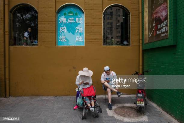 Chinese Hui Muslim couple sit outside a restaurant after Eid al-Fitr prayers marking the end of the holy fasting month of Ramadan at the historic...