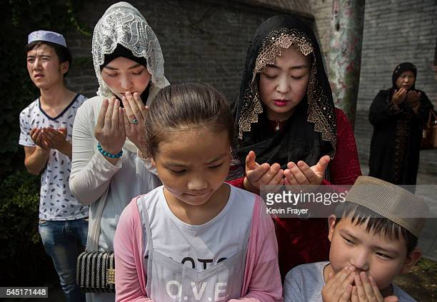 """Chinese Hui Muslim family prays at the """"Sheiks Tombs"""" after Eid al-Fitr prayers marking the end of the holy fasting month of Ramadan at the historic..."""