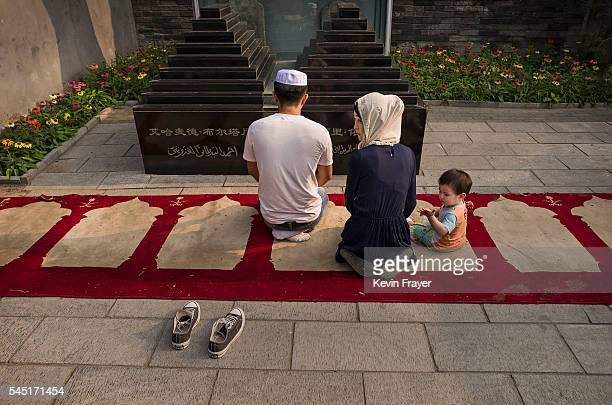 """Chinese Hui Muslim family prays at the """"Sheiks Tombs"""" before Eid al-Fitr prayers marking the end of the holy fasting month of Ramadan at the historic..."""