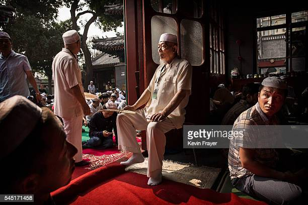 Chinese Hui Muslim guards the door as others prepare to pray during Eid al-Fitr prayers marking the end of the holy fasting month of Ramadan at the...