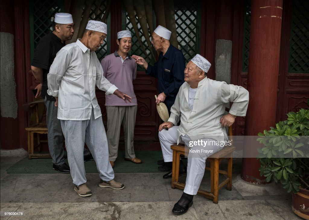 Chinese Hui Muslim men chat before Eid al-Fitr prayers marking the end of the holy fasting month of Ramadan at the historic Niujie Mosque on June 16, 2018 in Beijing, China. Islam in China dates back to the 10th century as the legacy of Arab traders who ventured from the Middle East along the ancient Silk Road. Of an estimated 23 million Muslims in China, roughly half are Hui, who are ethnically Chinese and speak Mandarin. China's constitution provides for Islam as one of five 'approved' religions in the officially atheist country though the government enforces severe limits. Worship is permitted only at state-sanctioned mosques and proselytizing in public is illegal. The Hui, one of 55 ethnic minorities in China (along with the Han majority), have long nurtured a coexistence with the Communist Party and is among the minority groups with political representation at various levels of government. The Hui Muslim population fast from dawn until dusk during Ramadan and it is believed there are more than 20 million members of the community in the country.