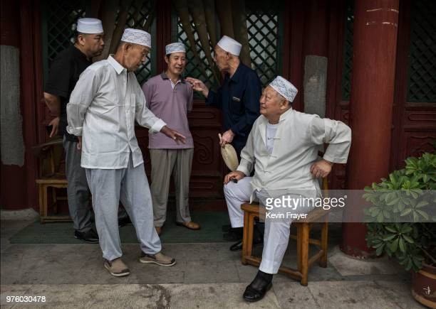 Chinese Hui Muslim men chat before Eid al-Fitr prayers marking the end of the holy fasting month of Ramadan at the historic Niujie Mosque on June 16,...