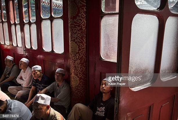 Chinese Hui Muslim men gather before Eid al-Fitr prayers marking the end of the holy fasting month of Ramadan at the historic Niujie Mosque on July...