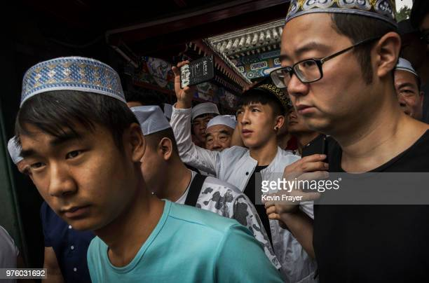 Chinese Hui Muslim men leave following Eid al-Fitr prayers marking the end of the holy fasting month of Ramadan at the historic Niujie Mosque on June...