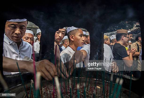 """Chinese Hui Muslim men light incense at the """"Sheiks Tombs"""" after Eid al-Fitr prayers marking the end of the holy fasting month of Ramadan at the..."""