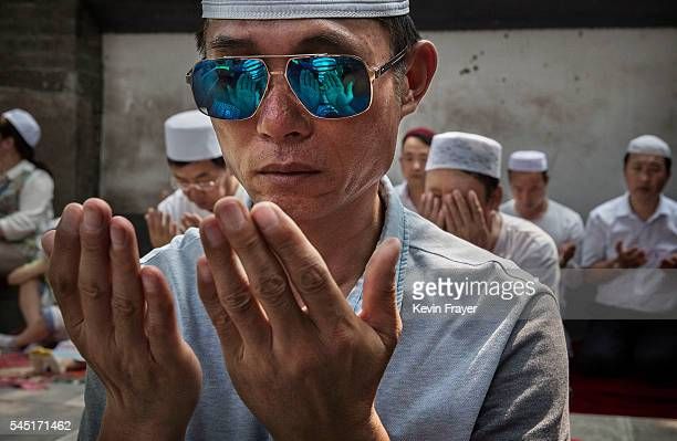 Chinese Hui Muslim men pray during Eid al-Fitr prayers marking the end of the holy fasting month of Ramadan at the historic Niujie Mosque on July 6,...