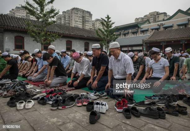 Chinese Hui Muslim men pray during Eid al-Fitr prayers marking the end of the holy fasting month of Ramadan at the historic Niujie Mosque on June 16,...