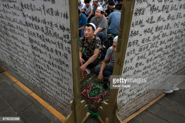 Chinese Hui Muslim men wait on a carpet before Eid al-Fitr prayers marking the end of the holy fasting month of Ramadan at the historic Niujie Mosque...