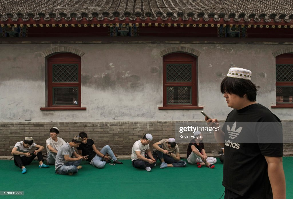 Chinese Hui Muslim men wait on a carpet before Eid al-Fitr prayers marking the end of the holy fasting month of Ramadan at the historic Niujie Mosque on June 16, 2018 in Beijing, China. Islam in China dates back to the 10th century as the legacy of Arab traders who ventured from the Middle East along the ancient Silk Road. Of an estimated 23 million Muslims in China, roughly half are Hui, who are ethnically Chinese and speak Mandarin. China's constitution provides for Islam as one of five 'approved' religions in the officially atheist country though the government enforces severe limits. Worship is permitted only at state-sanctioned mosques and proselytizing in public is illegal. The Hui, one of 55 ethnic minorities in China (along with the Han majority), have long nurtured a coexistence with the Communist Party and is among the minority groups with political representation at various levels of government. The Hui Muslim population fast from dawn until dusk during Ramadan and it is believed there are more than 20 million members of the community in the country.