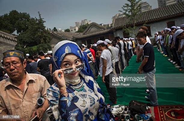 Chinese Hui Muslim woman arrives for Eid al-Fitr prayers marking the end of the holy fasting month of Ramadan at the historic Niujie Mosque on July...