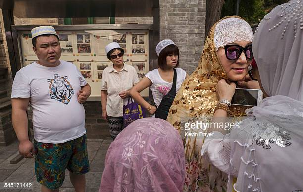Chinese Hui Muslim woman helps another with her headscarf before Eid al-Fitr prayers marking the end of the holy fasting month of Ramadan at the...