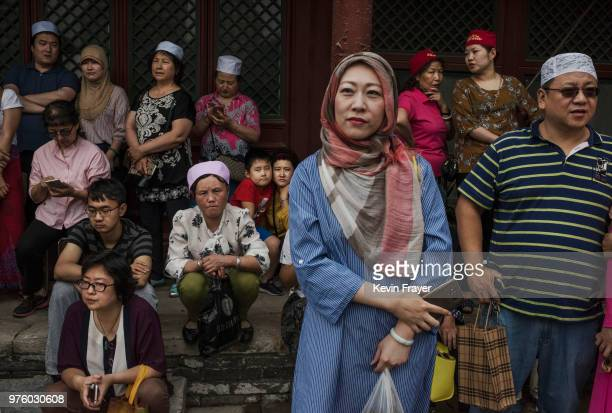 Chinese Hui Muslims and others wait before Eid al-Fitr prayers marking the end of the holy fasting month of Ramadan at the historic Niujie Mosque on...