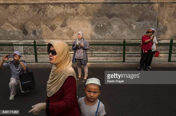 Chinese Hui Muslims arrive for Eid al-Fitr prayers marking the end of the holy fasting month of Ramadan at the historic Niujie Mosque on July 6, 2016...