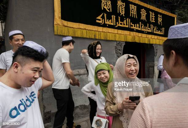 Chinese Hui Muslims greet each other after Eid al-Fitr prayers marking the end of the holy fasting month of Ramadan at the historic Niujie Mosque on...