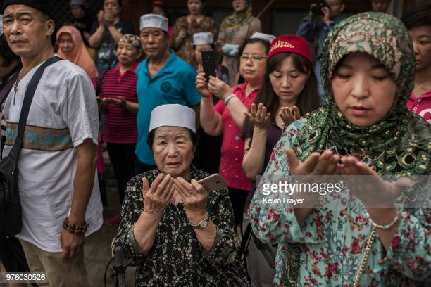 Chinese Hui Muslims pray during Eid al-Fitr prayers marking the end of the holy fasting month of Ramadan at the historic Niujie Mosque on June 16,...