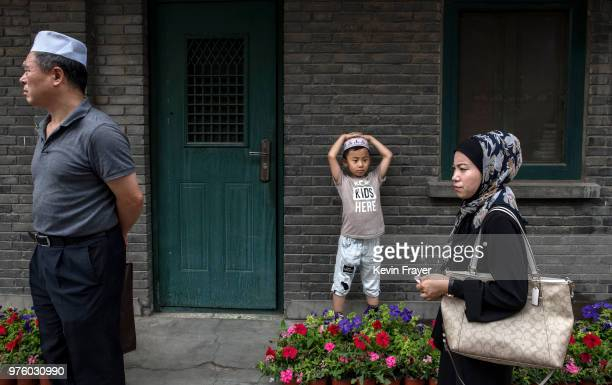 Chinese Hui Muslims wait before Eid al-Fitr prayers marking the end of the holy fasting month of Ramadan at the historic Niujie Mosque on June 16,...