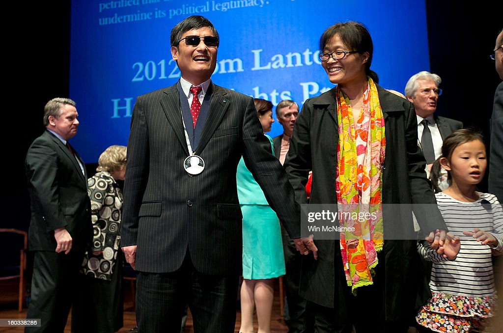 Chinese human rights activist Chen Guangcheng (3rd L) stands with his wife Yua Weijing (3rd R) following a ceremony where he was presented the Tom Lantos Human Rights Prize January 29, 2013 in Washington, DC. The Lantos Human Rights Prize is awarded each year and aims to raise awareness regarding human rights violations and the individuals dedicated to fighting them around the world.