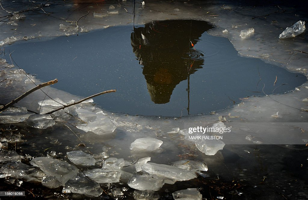 A Chinese ice fisherman is reflected in the water as he tries his luck in minus 3 Centigrade temperatures in the frozen Houhai Lake of Beijing on December 9, 2012. The fisherman, who were hoping to catch carp, share the lake with swimmers and ice skaters. AFP PHOTO/Mark RALSTON
