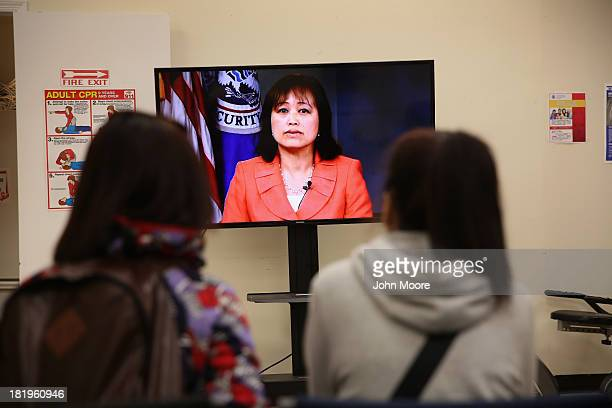 Chinese immigrants listen as a U.S. Immigration and Citizenship Services officer explains citizenship procedures via a video link on September 26,...